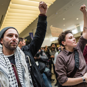 A man in a white and black keffiyeh scarf and woman in a burgundy short hold up their fists