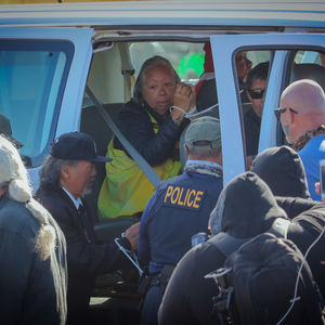 An elderly woman with gray hair sits handcuffed in a police car.
