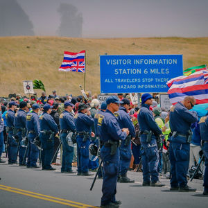 Dozens of police stand before protesters at the base of Mauna Kea