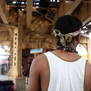 The back of a Black man wearing a white tank top underneath an elevated train.