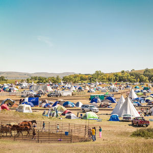 A wide shot of the Oceti Sakowin camp shows dozens of tipis and a circular grazing space for horses