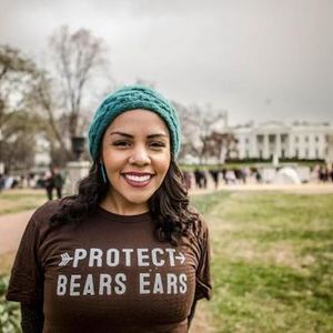 "A smiling young woman wearing a green knit hat and a brown T-shirt that says ""Protect Bears Ears"" stands with the White House in the background."