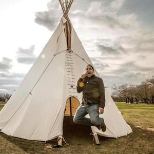 A man in an olive jacket talking on a mobile phone jumps into the air with a tipi in the background,