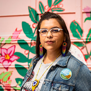 A Native woman wearing colorful beaded earrings and a denim jacket stands before a structure painted pink