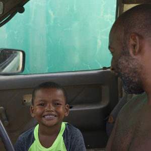 A smiling young boy in a yellow tank top sits next to his father in their van
