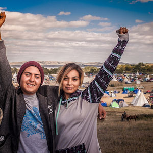 Wearing colorful casual clothes, Alex Howland and Jasilea Rose Charger put up power fists while standing in front of a white tipi at Oceti Sakowin camp.