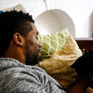 A Black man with a dark fade haircut and beard rests his head on a blue pillow.