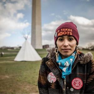 "A young woman wearing a maroon skullcap with yellow thread that spells out ""It takes roots"" stands in front a white tipi and the Washington Monument."