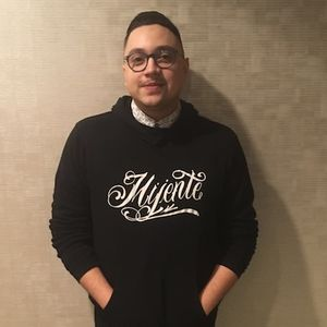 "Latino young man in a black hoodie that says ""mijente"""