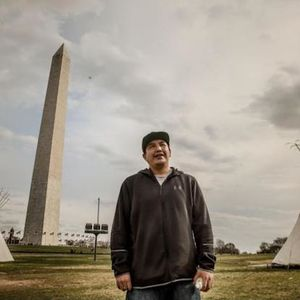 A tall man in a brown sweat jacket stands in front of two white tipis and the Washington Monument.