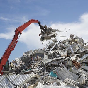 A crane looms over a large pile of metal refuse