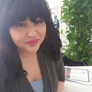 Lilianna Reyes sits at a table with an informational packet on the Michigan-based organization Orchards Childrens Services