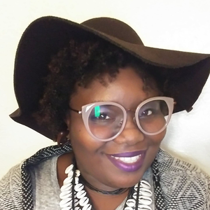 Rhiannon Chester smiles for a photo while wearing a brown floppy hat, round glasses, and a layered necklace made of seashells.