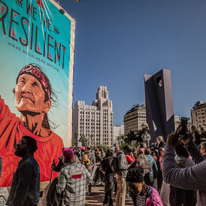 "Huge banner with an elderly Native woman with her fist up and the caption ""We the Resilient"" hangs on a wall in L.A. on a sunny day."
