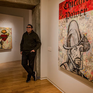 "Yerena stands next to a painting with a gray collage background and a large black stamp of a Spanish conquistador and the words ""Chicano power."""
