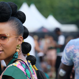 Black woman wears a ponytail and sunglasses with a bee on the bridge