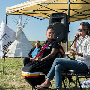 """Two women sit on chairs outside. One of them speaks into a microphone. In the background, another woman stares at them. They are all sitting beneath a pop-up tent. A flag peaks into the frame to the left. The letters inscribed say """"Sacred Stone Village."""""""
