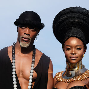 A Black man with a blonde beard poses with a Black woman wearing a headdress and bustier.