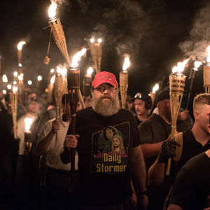 "A man with a gray beard wearing a black promotional T-shirt that says ""Daily Stormer"" marches holding a lit torch with hundreds of White nationalists doing the same"