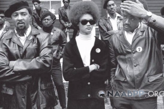 Black and white photo of three people wearing Black Panther Party buttons