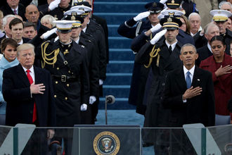 White woman in light blue skirt and coat, White man in navy suit and red tie, Black man in grey suit and blue tie and Black woman in maroon coat and skirt stand with hands on hearts in front of saluting military and others all standing on blue stairs