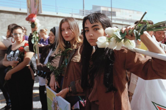 Brown woman holds white flowers with green stems and multi-colored sign in crowd with other Brown people against grey wall and blue sky