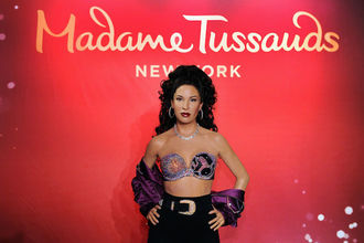 Wax statue of Brown woman in purple and black top and purple scarf and black pants in front of red screen with gold text