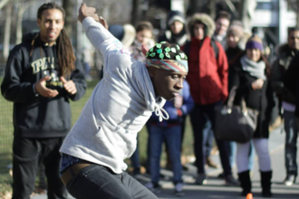 Black boy in grey hoodie and multicolored bandana and grey jeans and green plants in hair in front of crowd in multicolored clothing and grey pavement and green trees