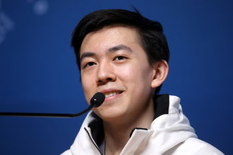 Asian teenage boy in white coat smiles behind black microphone and in front of blue wall
