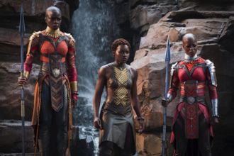 Two Black women in red and grey outfits hold grey spears next to Black woman in brown and gold outfit in front of brown cliff and clear waterfall