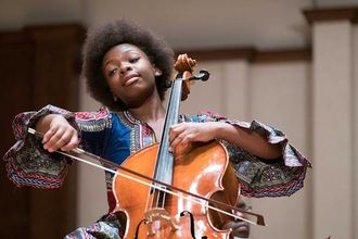 Black girl with black afro in blue and red and black and yellow patterned dress plays brown cello with brown bow in front of brown and beige walls