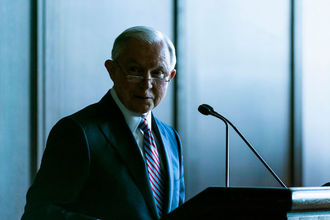 Jeff Sessions. White man with white hair, wire-rimmed glasses and suit smirks at the camera