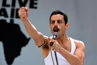 Rami Malek with black hair wears white tank top and black arm bracelet with silver spikes and black microphone in front of white background with black Live Aid logo