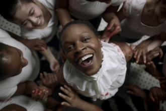 Screenshot of Black woman in white dress surrounded by Black and Asian women in white shirts on white floor with black tiles