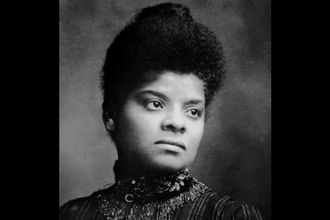 Black-and-white image of Ida B. Wells in black and white attire in front of grey background