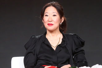 Sandra Oh in black shirt and blazer and red pants in front of dark grey background