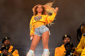 Beyoncé flips blond hair while wearing gold sweatshirt and blue jean shorts behind Black marching band members in yellow shirts and black hats in front of dark background with grey smoke