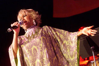 Celia Cruz sings into black microphone while wearing yellow and purple outfit in front of band in red light in front of black wall