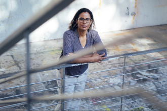 Kelly Lytle-Hernandez in blue patterned shirt and black glasses and white pants leans on grey metal handrail in front of white wall and brown floor with multicolored paint