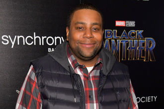 Kenan Thompson in black vest and black and red and white plaid shirt in front of black wall with white and red and blue text