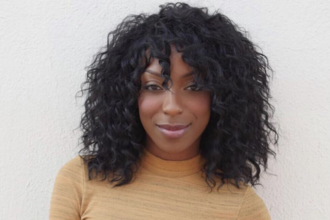 Ego Nwodim. Black woman with black curly hair in yellow-orange sweater in front of grey background