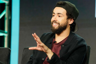 A young man of color with black bair and black beard wearing a black blazer, burgundy shirt and backwards baseball cap, smiles with one hand open in front of face as if for emphasis.