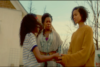 Three Black women hold hands in a circle outside with a farmhouse in the background.