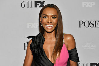 Janet Mock. Black woman with long hair in black and pink dress, standing in front of a white and back backdrop.