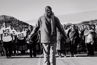 Mauna Kea protestors. Black and white image of crowd with main shot of man with back to camera.