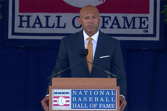 Mariano Rivera. Latinx man with bald head wearing dark suit, white shirt and red tie.