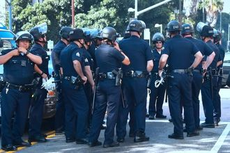 Large group of black-uniformed police officers gather on a sidewalk.