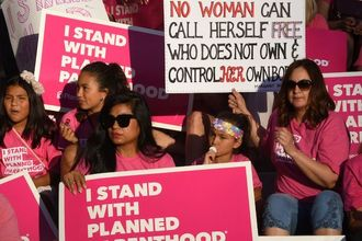 people holding signs in support of Planned Parenthood and reproductive rights