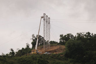 Damaged power lines on a hilltop in Patillas, Puerto Rico, against a gray sky
