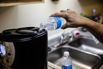 A Black person's hand pouring bottled water into a coffee maker